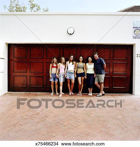 Stock Photo Of Family Holding Hands In Front Of Garage Doors