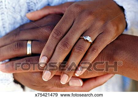Stock Photograph Of Hands Of Married Couple Wearing Wedding Rings