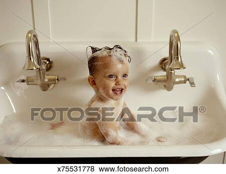 Pictures of Baby girl (9-12 months) taking bubble bath in sink ...