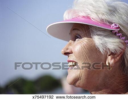 370c98a3 Senior woman wearing sun visor, smiling, close up, side view Stock ...