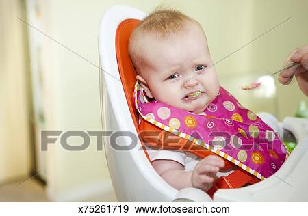 stock photograph of baby girl making a sad face while being fed