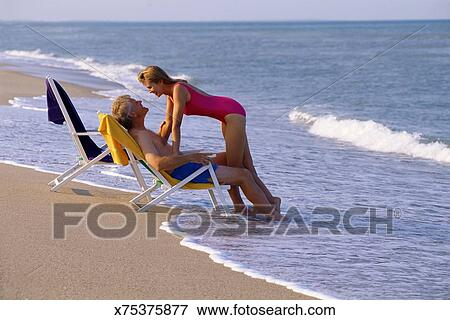 Couple on beach with lounge chairs & Picture of Couple on beach with lounge chairs x75375877 - Search ...