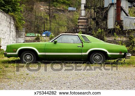 stock photo of old broken down green car rusting away x75344282