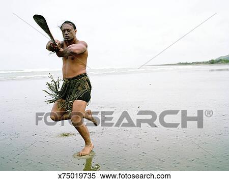 eaf79120a Maori man performing Haka Powhiri on beach Stock Photography ...