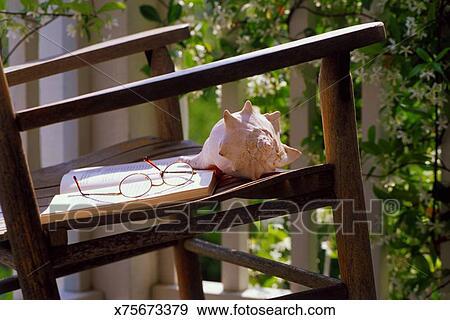 Archivio fotografico occhiali libro e conchiglia su sedia