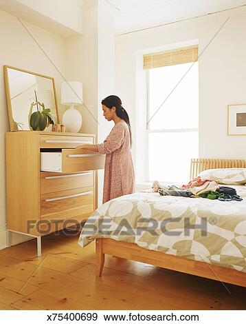 Bedroom side view Bed Room Stock Photograph Young Woman Looking In Dresser Drawer In Bedroom Side View Fotosearch Fotosearch Stock Photograph Of Young Woman Looking In Dresser Drawer In Bedroom