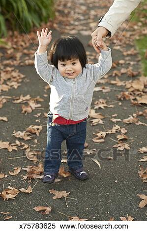 1 year old Chinese girl standing outside