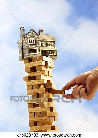 Toy house balancing on tower of wooden bricks, mans hand removing one block  Stock Image