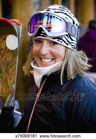 9642582d8c5 Stock Photography - Woman holding skis and wearing ski attire. Fotosearch -  Search Stock Photos