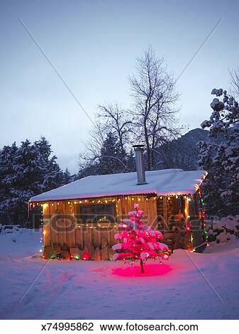 Log Cabin Christmas.Log Cabin Decorated With Christmas Lights In Snow At Dusk Stock Image