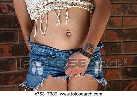Stock Photograph Of Woman With Belly Button Piercing In Cut Off