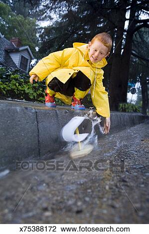 Boy launching homemade boat in gutter after rain Stock Image