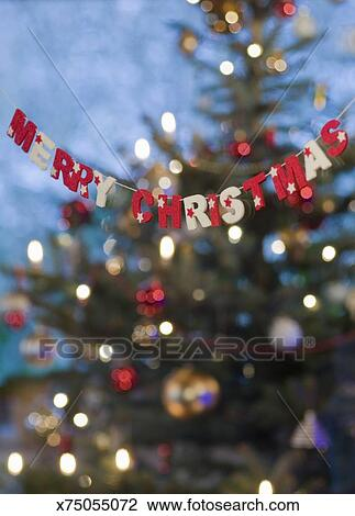Felt Merry Christmas Garland In Front Of Christmas Tree Stock Image