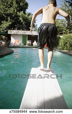 Boy about to jump off diving board into swimming pool ...