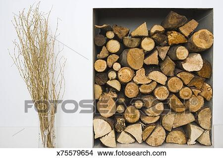 Stock Photo Of Gold Sprayed Sticks In A Vase Next To A Log Pile