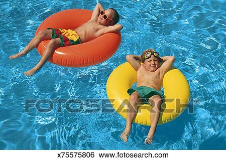 Young boys floating in inner tubes in swimming pool Stock ...