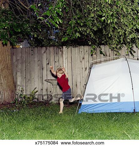 Boy (4-6) jumping out of tent pitched in yard arms raised side view & Stock Photo of Boy (4-6) jumping out of tent pitched in yard arms ...