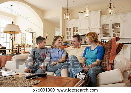 Family Relaxing On Couch At Home