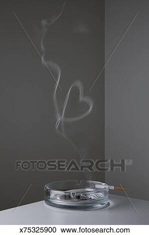 Cigarette on ashtray makes heart-shape smoke ring