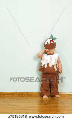Christmas Pudding Outfit.Unhappy Baby Boy In Christmas Pudding Outfit Stock Photo