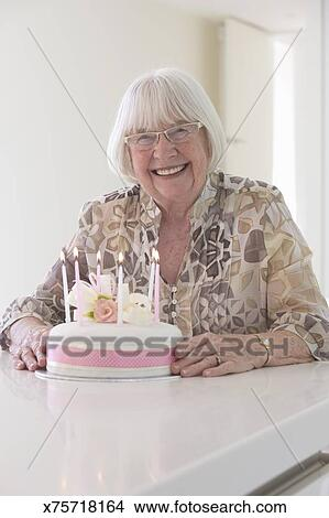 Smiling Elderly Woman Holding A Cake