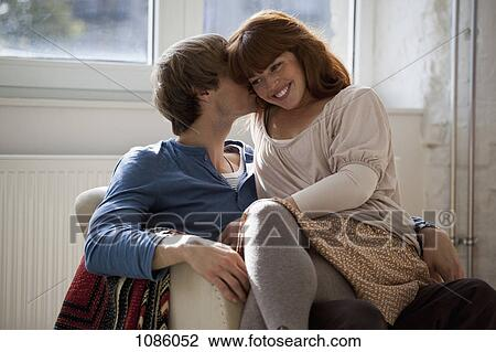 Stock photo of a young man kissing his girlfriend whos sitting on a young man kissing his girlfriend whos sitting on his lap altavistaventures Image collections