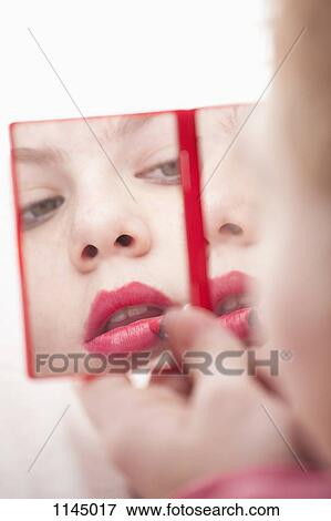 hand holding mirror. Girl Holding Hand Mirror And Applying Lipstick