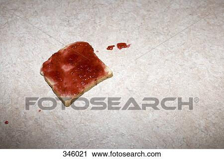 stock photography of slice of toast with strawberry jam dropped on