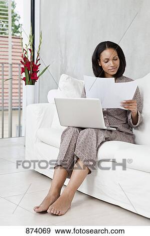 comprare popolare 2acb4 3ad9f Uno, donna, in, pigiama, usando, uno, laptop, e, guardando documenti  Archivio Fotografico