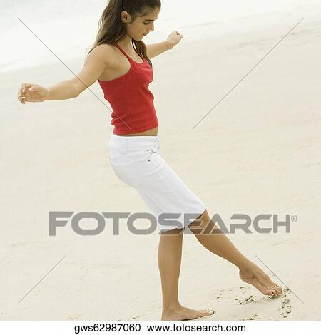 stock photography of side profile of a girl drawing in the sand with