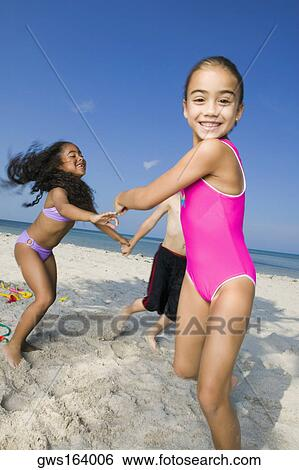 Two Girls And Boy Playing On The Beach Stock Photograph