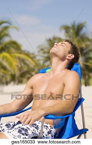 Stock Photo Young Man Relaxing On A Lounge Chair At The Beach Fotosearch