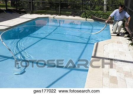 Mature man cleaning a swimming pool with a hose Stock Image ...