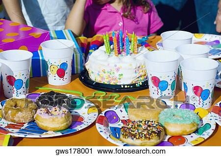 Birthday Cake And Donuts With Presents On A Table
