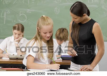 Female Teacher Teaching A Schoolgirl With Other Students Sitting In The Background