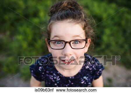 2f05499e12 Portrait of cute girl wearing eye glasses looking up at camera Stock ...