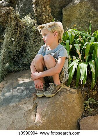 stock photo of pensive boy sitting on rock is0990994 search stock
