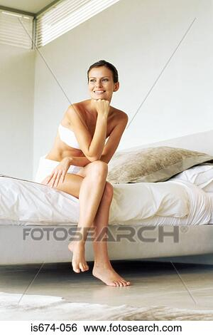 775493cc836 Woman sitting on the edge of her bed Stock Photograph | is674-056 ...