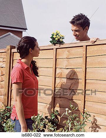 man and woman talking over garden fence stock photo is680 022