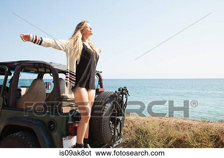 Stock Images Of Young Woman Standing On Back Of Jeep At Coast With
