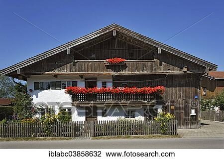 stock photo of old farm balcony with geraniums aying upper