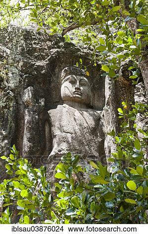 rock verlichting boeddha figuur achter brink loof verhevene hand bescherming gebaar mahayana boeddhisme dowa rots tempel dichtbij bandarawela