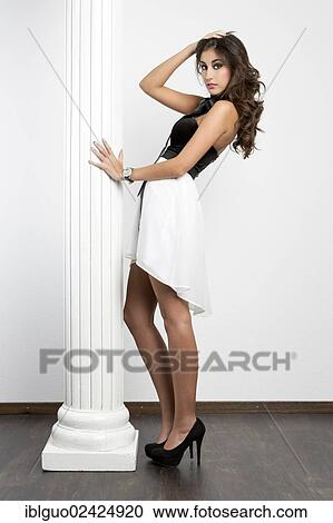 1fc4801572 Stock Photography - Young woman with a black top, short white skirt and  black high