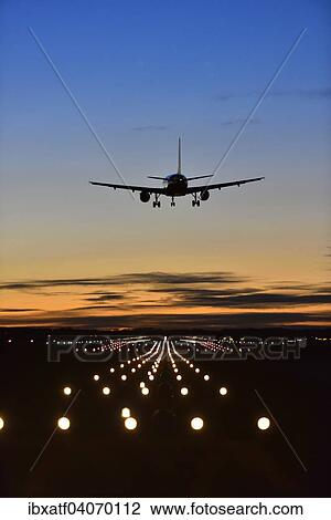 Aircraft landing at sunset, Airbus, runway, landing lights, Munich Airport  Franz Josef Strauss, Munich, Upper Bavaria, Bavaria, Germany, Europe Stock