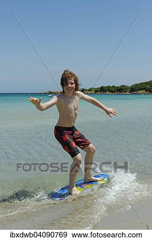Boy Surfing With His Boogie Board Beach Or Skimboard On The Bay Of Rondinara Southeast Coast Corsica France Europe