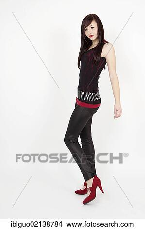 eed160165ee7fe Picture - Young woman wearing a black top, latex leggings and red high  heels.