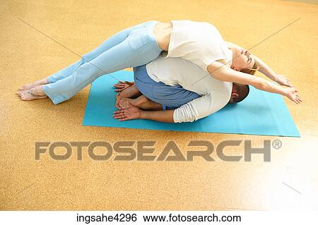 Couple In Fish And Child Poses Of Partner Yoga Practice Stock Photograph Ingsahe4296 Fotosearch