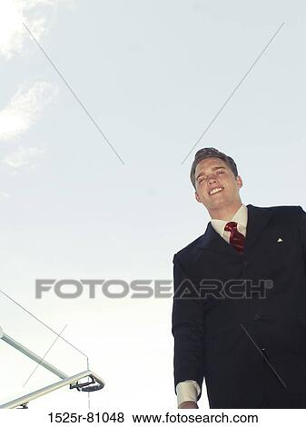 72716bac90fa ... walking down steps Stock Photo. Stock Photo - Younger business man in black  suit and red tie smiles as he stands