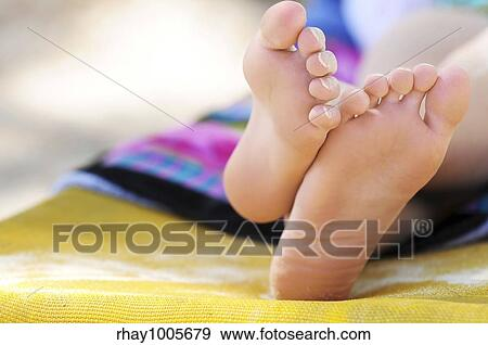 stock photograph of closeup of feet of a young girl in chaise lounge