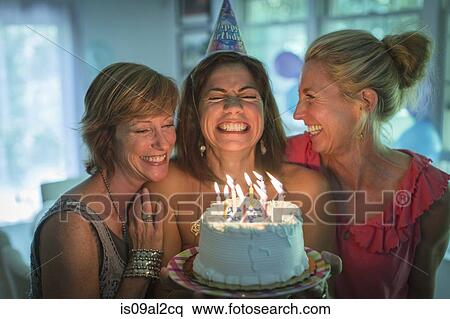 Stupendous Mature Woman Holding Birthday Cake Making Wish While Two Friends Funny Birthday Cards Online Sheoxdamsfinfo